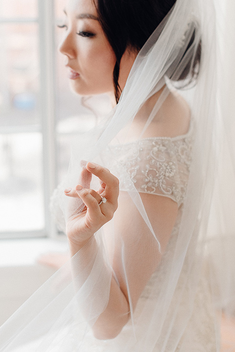 occidental-college-wedding-bride-putting-on-shoes-bride-in-a-fitted-gown-with-a-beaded-bodice