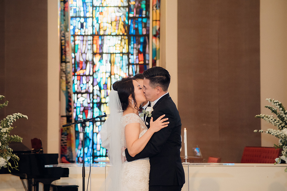occidental-college-wedding-first-kiss-groom-in-black-tuxedo-bride-in-a-fitted-gown-with-a-beaded-bodice