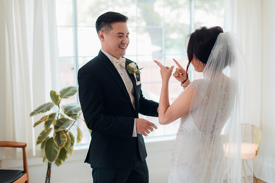 occidental-college-wedding-first-look-groom-in-black-tuxedo-bride-in-a-fitted-gown-with-a-beaded-bodice