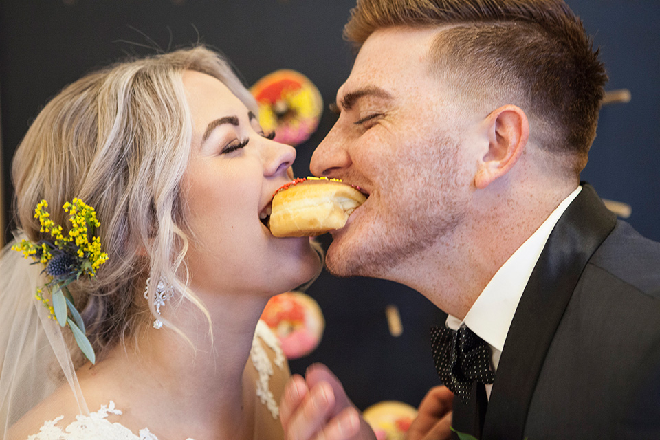 parq-west-shoot-couple-eating-the-donut-bride-wearing-a-flowing-gown-with-an-illusion-lace-bodice-and-cap-sleeves-groom-in-a-charcoal-tuxedo-with-a-black-satin-shawl-lapel