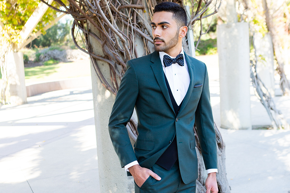 green-suit-coat-and-pants-with-a-black-vest-and-patterned-bow-tie