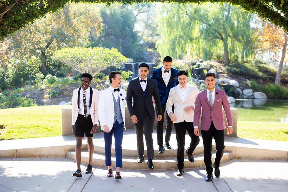 group-walking-down-stairs-in-their-wide-array-of-tuxedo-colors-for-prom
