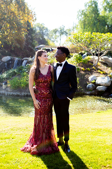 girl-wearing-a-deep-red-prom-dress-and-boy-wearing-a-navy-shawl-lapel-tuxedo-with-navy-pants