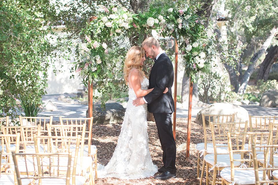 rockwood-shoot-bride-and-groom-at-ceremony-space-bride-in-a-ball-gown-with-her-hair-down-and-blingy-jewelry-groom-in-a-traditional-black-tuxedo-with-black-bow-tie