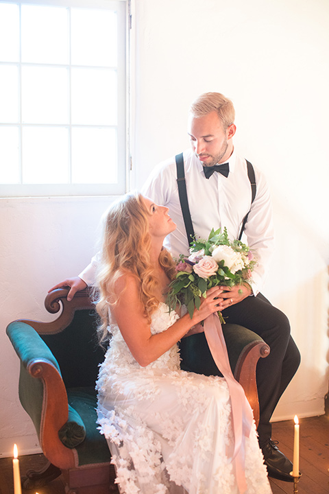 rockwood-shoot-bride-and-groom-in-chair-looking-at-each-other-bride-in-a-ball-gown-with-hair-down-and-groom-in-black-tuxedo