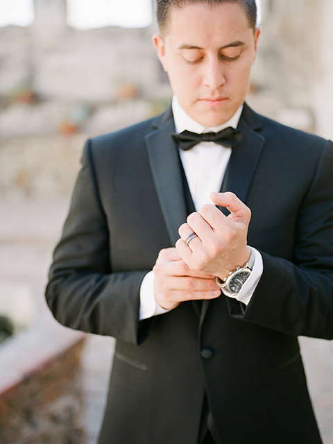 san-juan-capastrano-wedding-close-up-groom-fixing-sleeve-groom-in-a-black-tuxedo-with-black-bow-tie