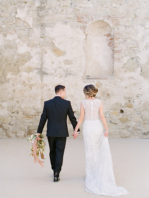 san-juan-capastrano-wedding-couple-walking-away-bride-in-a-white-fitted-silk-dress-with-cap-sleeves-and-an-illusion-neckline-and-back-groom-in-a-black-tuxedo-with-black-bow-tie