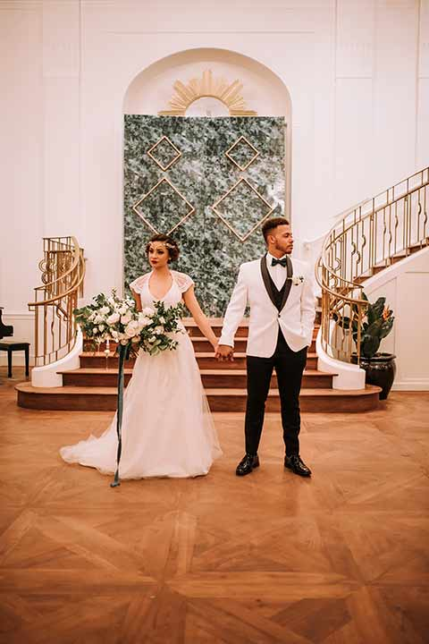santa-anita-park-art-deco-shoot-brid-and-groom-looking-in-opposite-directions-at-altar-bride-wearing-a-vintage-inspired-dress-with-delicate-beading-and-flutter-sleeves-groom-wearing-a-white-tuxedo-jacket-with-black-trim-and-black-pants