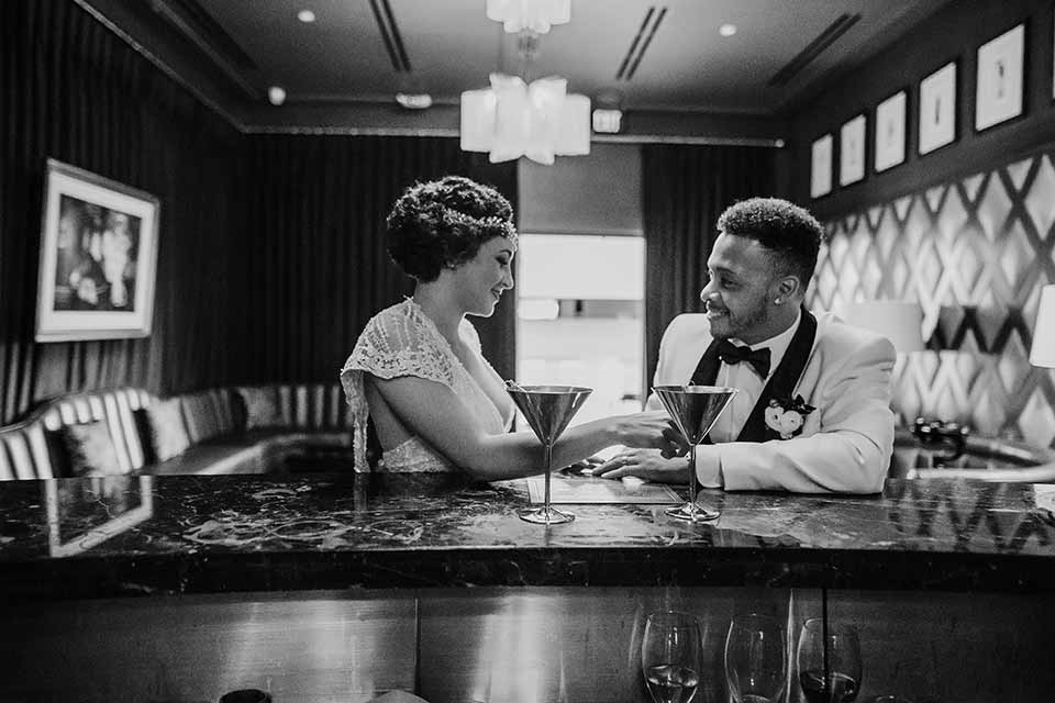santa-anita-park-art-deco-shoot-bride-and-groom-black-and-white-photo-of-them-at-bar -bride-wearing-a-vintage-inspired-dress-with-delicate-beading-and-flutter-sleeves-groom-wearing-a-white-tuxedo-jacket-with-black-trim-and-black-pants