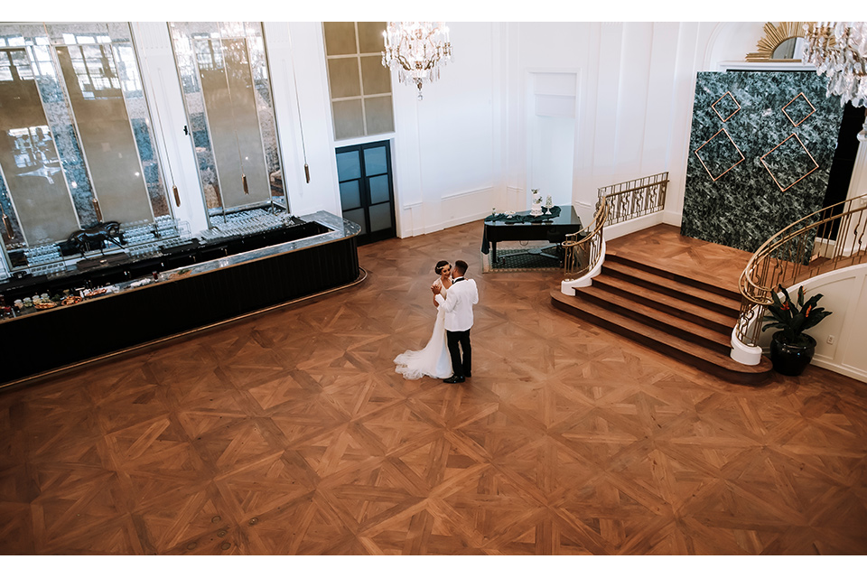 santa-anita-park-art-deco-shoot-bride-and-groom-dancing-bride-and-groom-black-and-white-photo-of-them-at-bar -bride-wearing-a-vintage-inspired-dress-with-delicate-beading-and-flutter-sleeves-groom-wearing-a-white-tuxedo-jacket-with-black-trim-and-black-pants