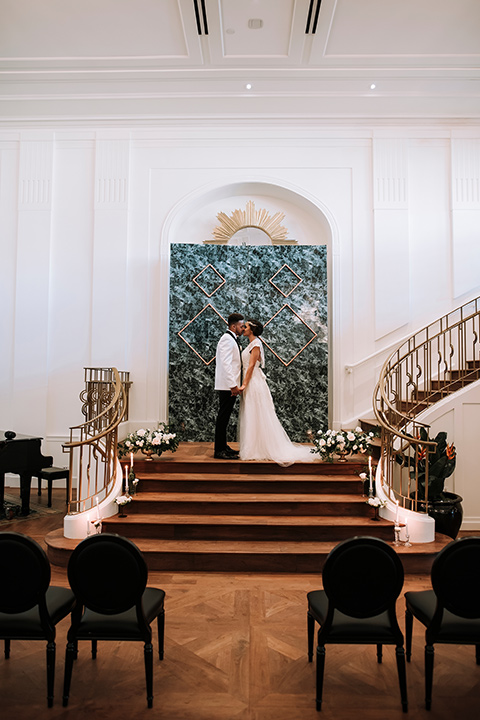 santa-anita-park-art-deco-shoot-bride-and-groom-kissing-far-away-bride-wearing-a-vintage-inspired-dress-with-delicate-beading-and-flutter-sleeves-groom-wearing-a-white-tuxedo-jacket-with-black-trim-and-black-pants