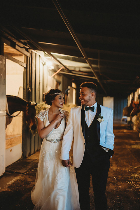 santa-anita-park-art-deco-shoot-bride-and-groom-walking-by-horses-bride-wearing-a-vintage-inspired-dress-with-delicate-beading-and-flutter-sleeves-groom-wearing-a-white-tuxedo-jacket-with-black-trim-and-black-pants