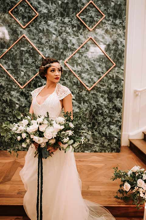 santa-anita-park-art-deco-shoot-bride-looking-to-the-side-bride-wearing-a-vintage-inspired-dress-with-delicate-beading-and-flutter-sleeves-groom-wearing-a-white-tuxedo-jacket-with-black-trim-and-black-pants