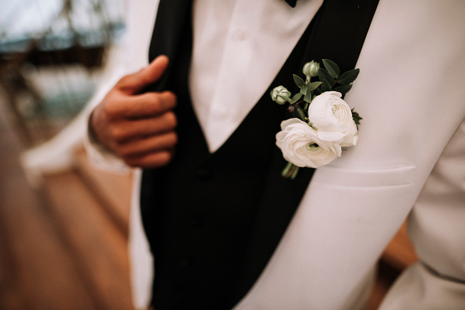 santa-anita-park-art-deco-shoot-close-up-on-jacket-bride-wearing-a-vintage-inspired-dress-with-delicate-beading-and-flutter-sleeves-groom-wearing-a-white-tuxedo-jacket-with-black-trim-and-black-pants