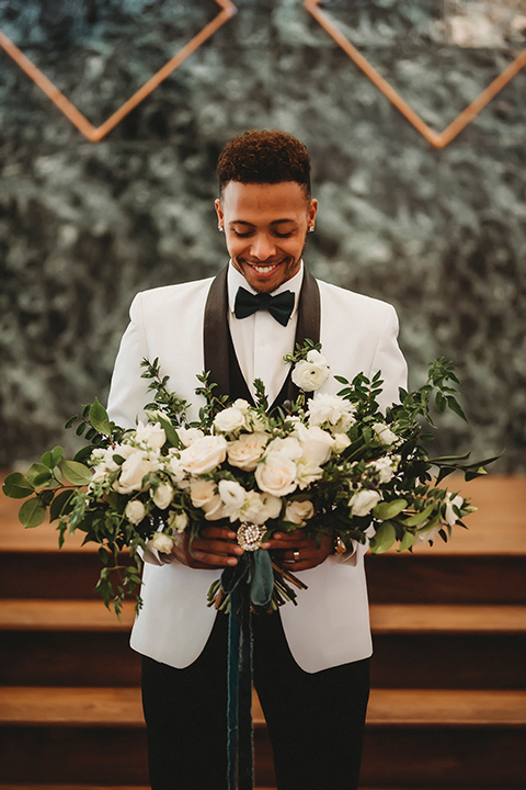 santa-anita-park-art-deco-shoot-groom-holding-flowers-groom-wearing-a-white-tuxedo-jacket-with-black-trim-and-black-pants