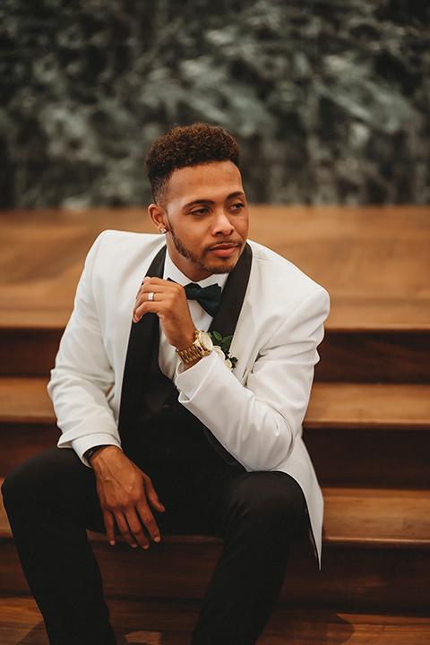 santa-anita-park-art-deco-shoot-groom-sitting-groom-holding-flowers-groom-wearing-a-white-tuxedo-jacket-with-black-trim-and-black-pants