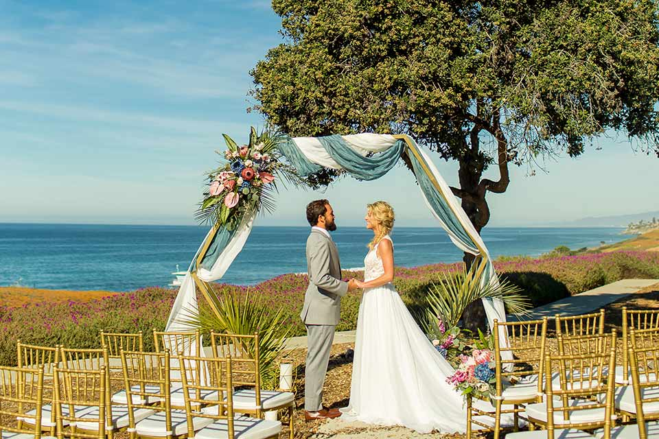 resized-image-seapoint-bridal-shoot-ceremony-bride-in-a-lace-gown-with-thick-lace-straps-and-hair-in-a-loose-braid-groom-in-a-light-grey-suit-with-a-white-long-tie