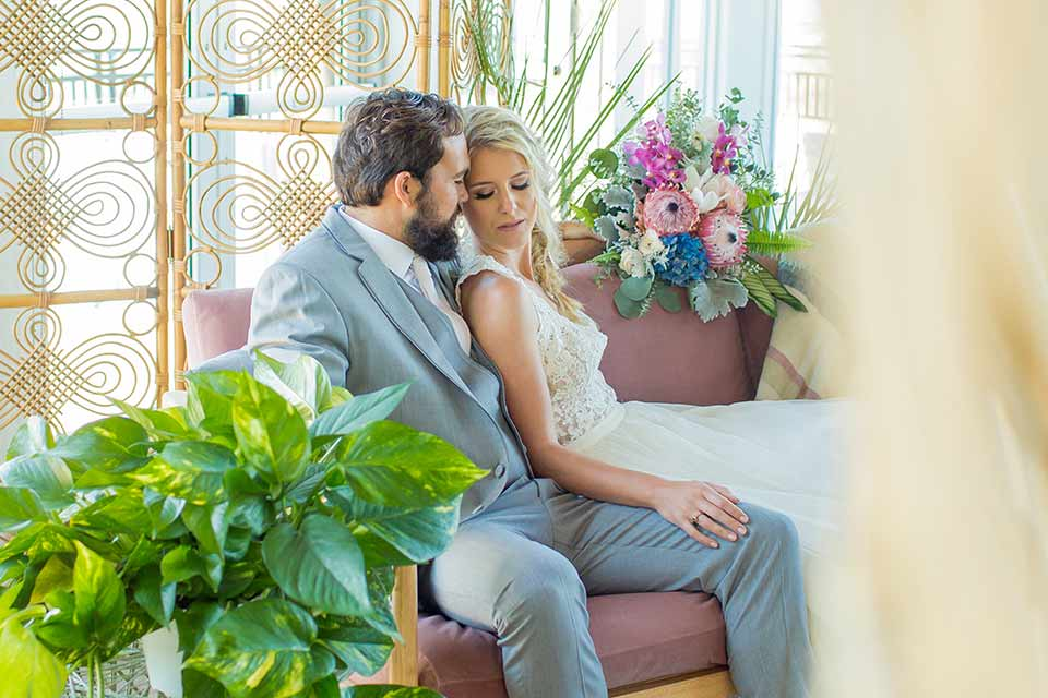 resized-seapoint-bridal-shoot-bride-and-groom-on-couch-bride-in-a-lace-gown-with-thick-lace-straps-and-hair-in-a-loose-braid-groom-in-a-light-grey-suit-with-a-white-long-tie