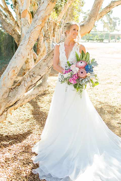 seapoint-bridal-shoot-bride-alone-with-florals-bride-in-a-lace-gown-with-thick-lace-straps-and-hair-in-a-loose-braid