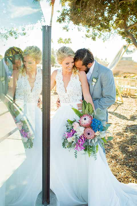 seapoint-bridal-shoot-bride-and-groom-laughing-bride-in-a-lace-gown-with-thick-lace-straps-and-hair-in-a-loose-braid-groom-in-a-light-grey-suit-with-a-white-long-tie