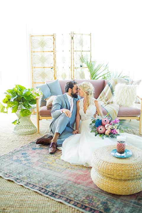 seapoint-bridal-shoot-bride-and-groom-on-the-floor-bride-in-a-lace-gown-with-thick-lace-straps-and-hair-in-a-loose-braid-groom-in-a-light-grey-suit-with-a-white-long-tie