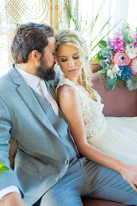 seapoint-bridal-shoot-bride-and-groom-sitting-eyes-closed-bride-in-a-lace-gown-with-thick-lace-straps-and-hair-in-a-loose-braid-groom-in-a-light-grey-suit-with-a-white-long-tie