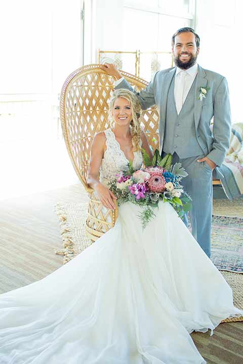 seapoint-bridal-shoot-bride-in-chair-groom-next-to-her-bride-in-a-lace-gown-with-thick-lace-straps-and-hair-in-a-loose-braid-groom-in-a-light-grey-suit-with-a-white-long-tie