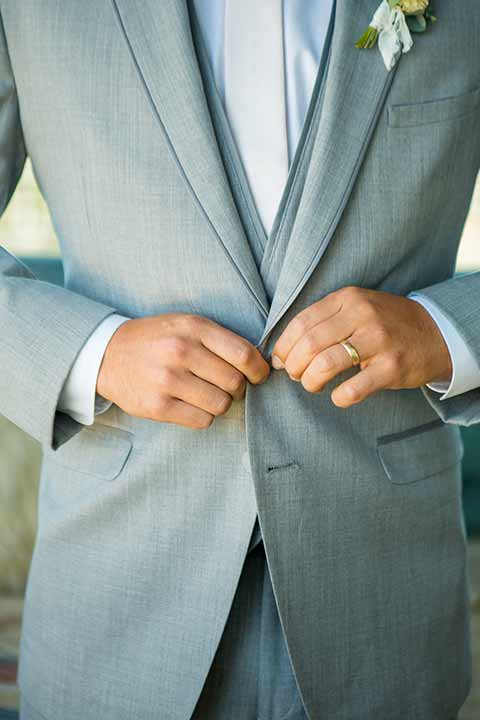 seapoint-bridal-shoot-close-up-on-the-suit-groom-in-a-light-grey-suit-with-a-white-long-tie