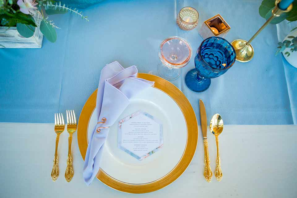 seapoint-bridal-shoot-table-settings-blue-linen-gold-and-pink-accents