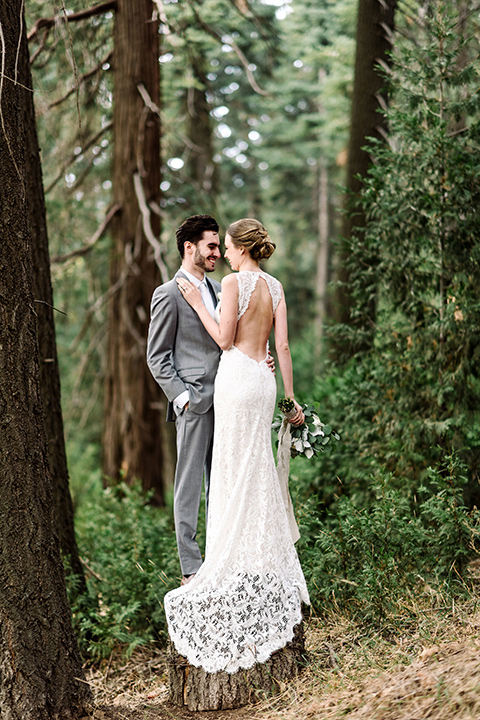 skypark-styled-shoot-bride-and-groom-near-trees-bride-in-lace-fitted-dress-with-a-sleeves-and-a-keyhole-back-detail-groom-in-grey-suit-with-brown-shoes-and-ivory-long-tie