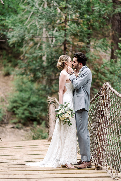 skypark-styled-shoot-bride-and-groom-on-bridge-bride-in-lace-fitted-dress-with-a-sleeves-and-a-keyhole-back-detail-groom-in-grey-suit-with-brown-shoes-and-ivory-long-tie