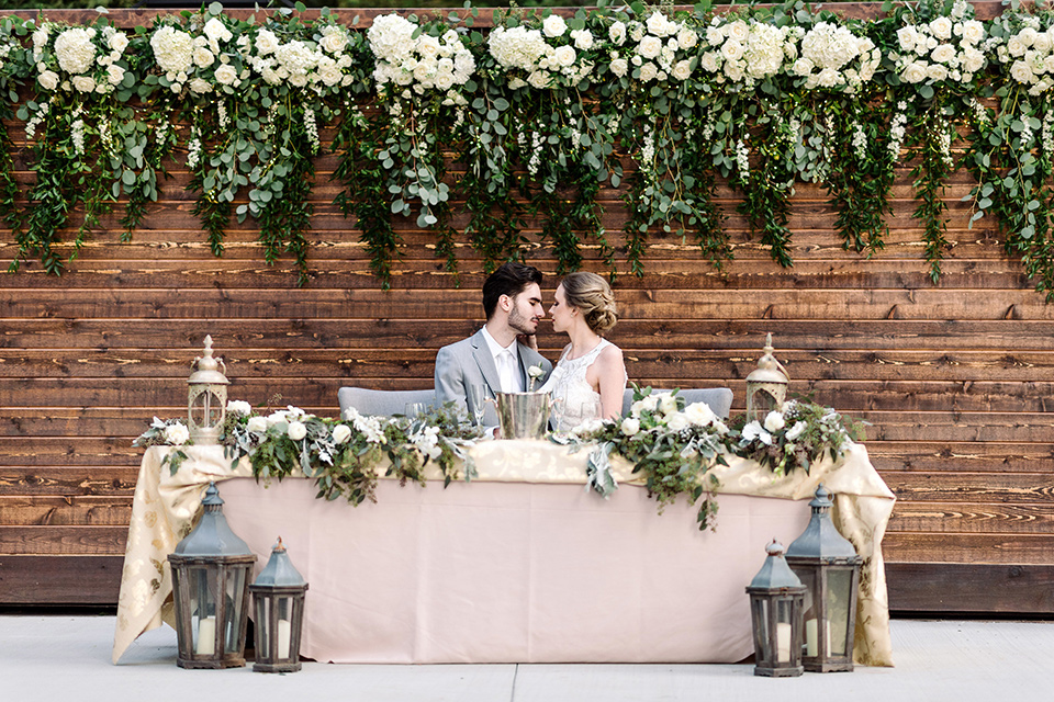 skypark-styled-shoot-bride-and-groom-sweetheart-table-bride-in-lace-fitted-dress-with-ca-sleeves-and-a-keyhole-back-detail-groom-in-grey-suit-with-brown-shoes-and-ivory-long-tie