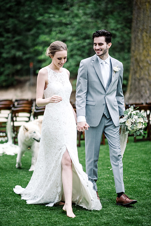 skypark-styled-shoot-bride-and-groom-walking-dog-behind-them-bride-in-lace-fitted-dress-with-a-sleeves-and-a-keyhole-back-detail-groom-in-grey-suit-with-brown-shoes-and-ivory-long-tie