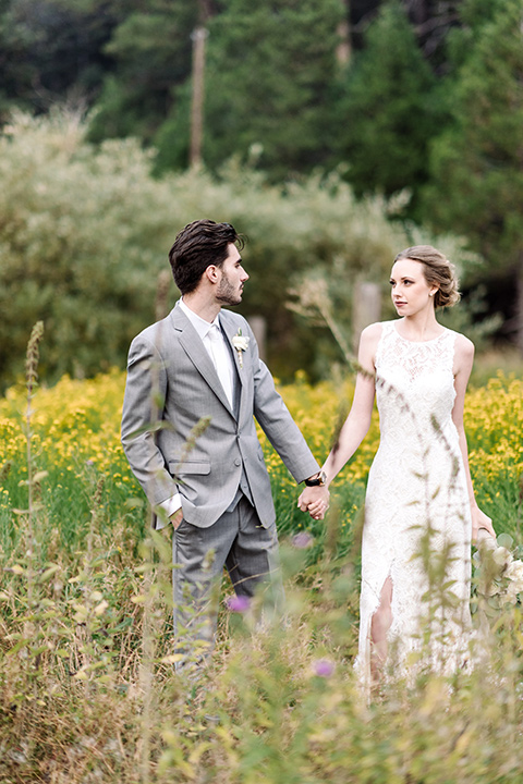 skypark-styled-shoot-bride-and-groom-walking-in-floral-fields-bride-in-lace-fitted-dress-with-a-sleeves-and-a-keyhole-back-detail-groom-in-grey-suit-with-brown-shoes-and-ivory-long-tie