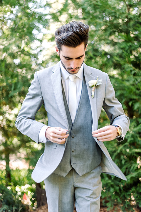 skypark-styled-shoot-groom-putting-on-jacket-groom-in-grey-suit-with-brown-shoes-and-ivory-long-tie