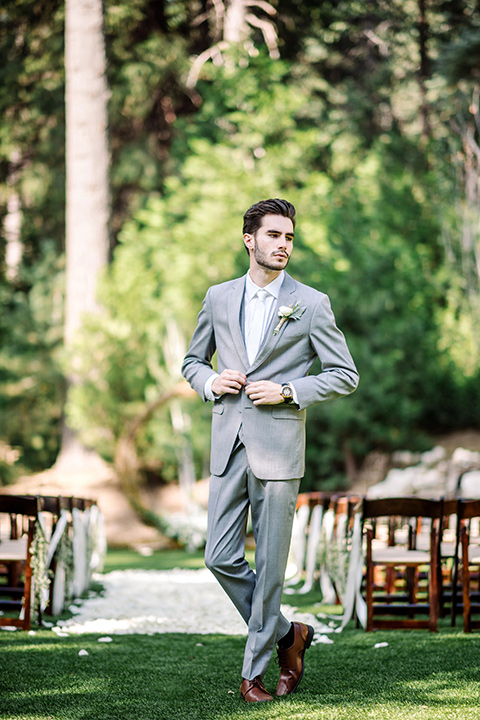 skypark-styled-shoot-groom-standing-groom-putting-on-jacket-groom-in-grey-suit-with-brown-shoes-and-ivory-long-tie