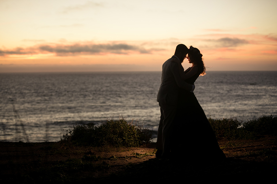 Terranea-styled-shoot-bride-and-groom-at-sunset-bride-in-a-midnight-blue-dress-with-an-illusion-neckline-with-jewels-on-bodice-her-hair-down-in-a-loose-wave-groom-in-a-light-grey-suit-with-a-blue-bow-tie-to-match-the-bride
