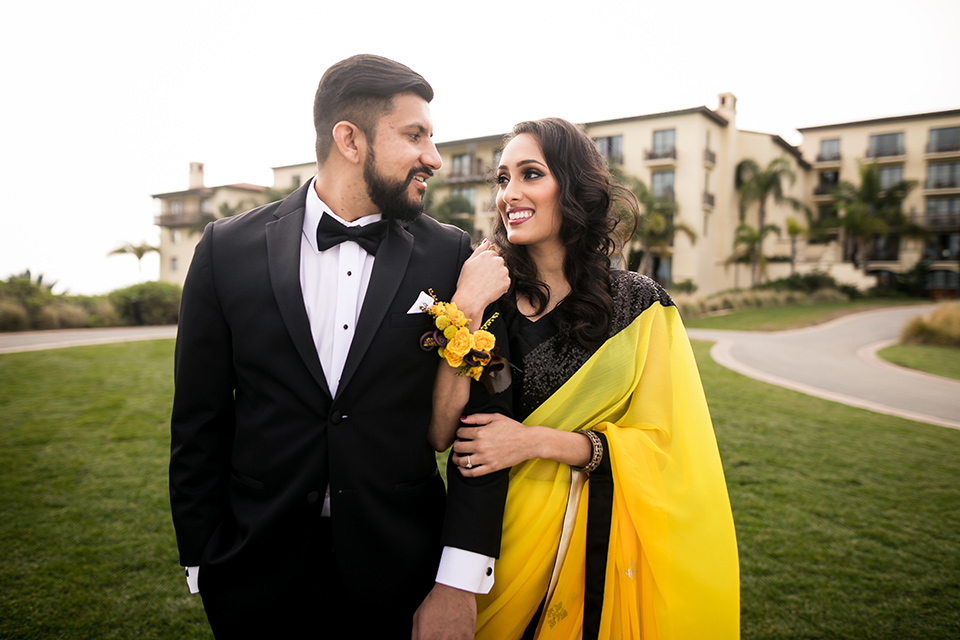 Terranea-styled-shoot-bride-and-groom-close-up-smiling-looking-at-each-other-bride-in-yellow-sarees-with-hair-in-a-loose-wave-groom-in-a-tradtitional-black-tuxedo-with-a-black-bowtie-and-black-vest