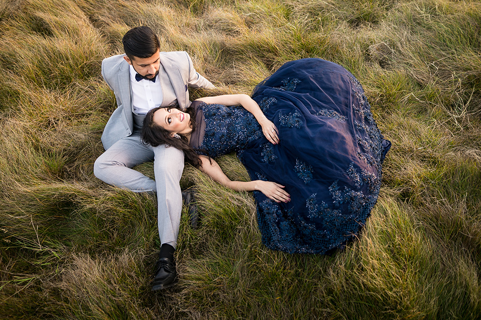 Terranea-styled-shoot-bride-and-groom-laying-in-the-grass-bride-in-a-midnight-blue-dress-with-an-illusion-neckline-with-jewels-on-bodice-her-hair-down-in-a-loose-wave-groom-in-a-light-grey-suit-with-a-blue-bow-tie-to-match-the-bride