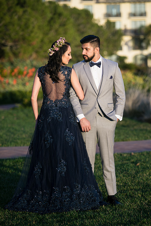 Terranea-styled-shoot-bride-in-blue-dress-and-crown-back-towards-to-the-camera-groom-in-grey-facing-camera-bride-in-a-midnight-blue-dress-with-an-illusion-neckline-with-jewels-on-bodice-her-hair-down-in-a-loose-wave-groom-in-a-light-grey-suit-with-a-blue-bow-tie-to-match-the-bride