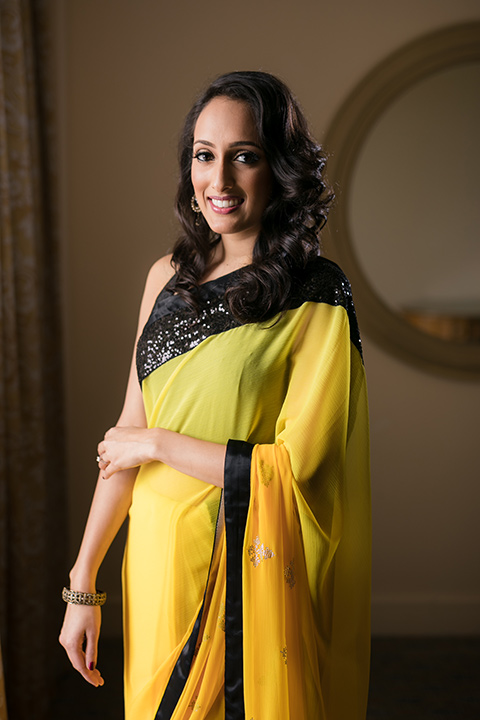 Terranea-styled-shoot-bride-in-yellow-dress-smiling-at-camera-bride-in-yellow-sarees-with-hair-in-a-loose-wave-with-gold-teardrop-earrings