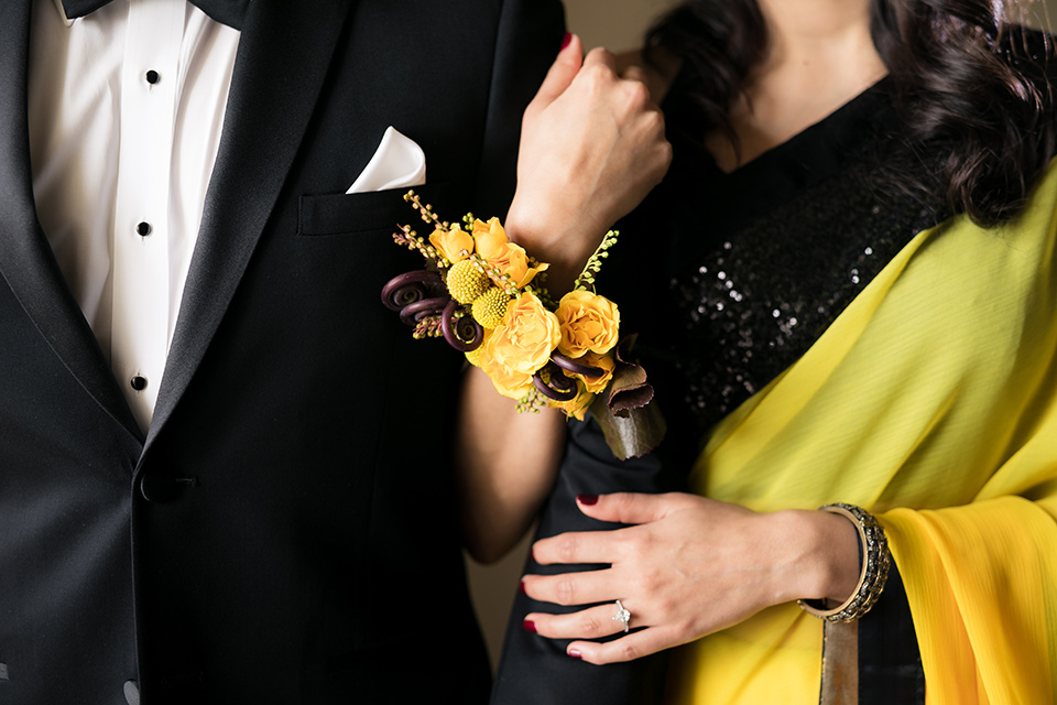 Terranea-styled-shoot-close-up-of-florals-bride-in-yellow-sarees-with-hair-in-a-loose-wave-groom-in-a-tradtitional-black-tuxedo-with-a-black-bowtie-and-black-vest-with-wearing-a-black-and-yellow-florals