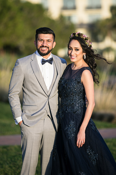 Terranea-styled-shoot-grey-and-blue-looks-both-smiling-at-camera-bride-in-a-midnight-blue-dress-with-an-illusion-neckline-with-jewels-on-bodice-her-hair-down-in-a-loose-wave-groom-in-a-light-grey-suit-with-a-blue-bow-tie-to-match-the-bride