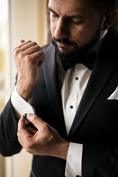 Terranea-styled-shoot-groom-fixing-cufflinks-groom-in-a-traditonal-black-tuxedo-with-black-bow-tie-and-black-studs-and-cufflinks