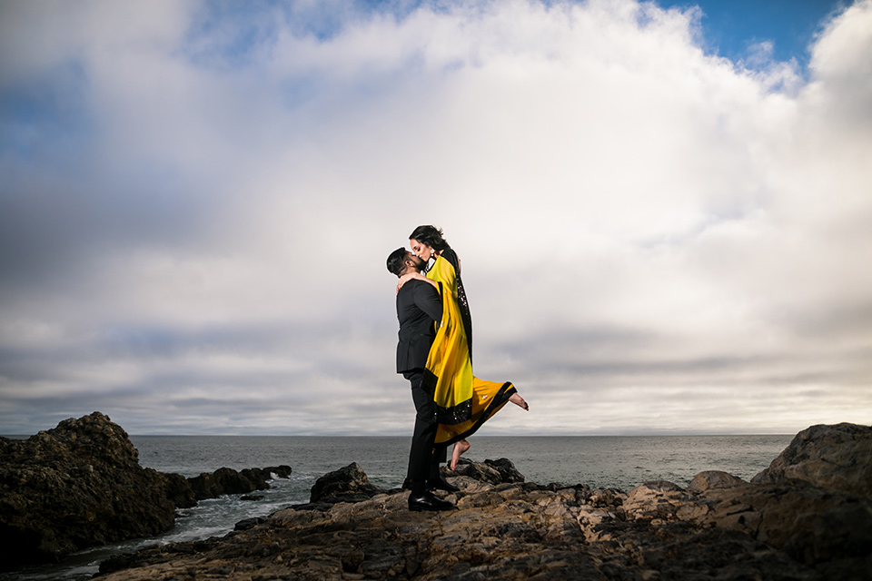Terranea-styled-shoot-groom-holding-up-bride-kissing-bride-in-yellow-bride-in-yellow-sarees-with-hair-in-a-loose-wave-groom-in-a-tradtitional-black-tuxedo-with-a-black-bowtie-and-black-vest-with-wearing-a-black-and-yellow-florals