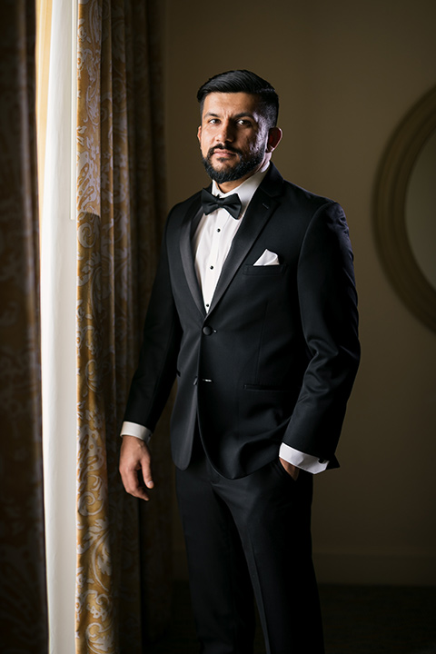 Terranea-styled-shoot-groom-looking-at-camera-groom-fixing-cufflinks-groom-in-a-traditonal-black-tuxedo-with-black-bow-tie-and-black-studs-and-cufflinks