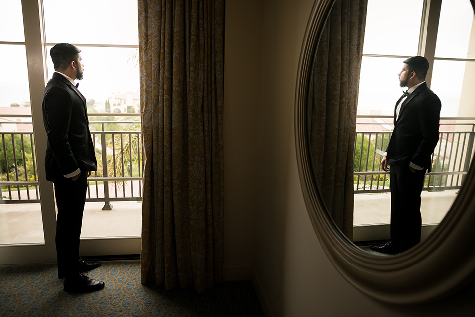 Terranea-styled-shoot-groom-looking-out-the-window-with-mirror-photo-groom-in-a-tradtitional-black-tuxedo-with-a-black-bowtie-and-black-vest