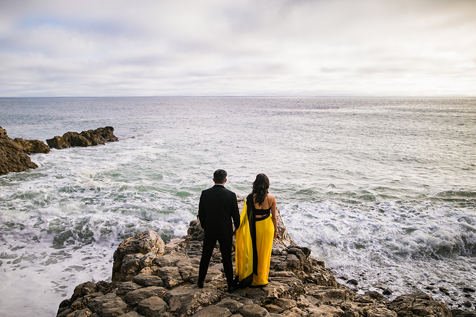 Terranea-styled-shoot-on-the-water-both-facing-the-ocean-bride-kissing-bride-in-yellow-bride-in-yellow-sarees-with-hair-in-a-loose-wave-groom-in-a-tradtitional-black-tuxedo-with-a-black-bowtie-and-black-vest-with-wearing-a-black-and-yellow-florals
