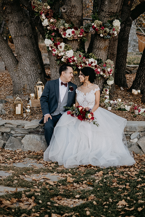 the-guest-ranch-bride-and-groom-sitting-by-ceremony-space-groom-in-a-dark-grey-suit-with-light-grey-vest-and-burgundy-bow-bride-in-a-tulle-ball-gown-with-straps-and-a-beaded-bodice