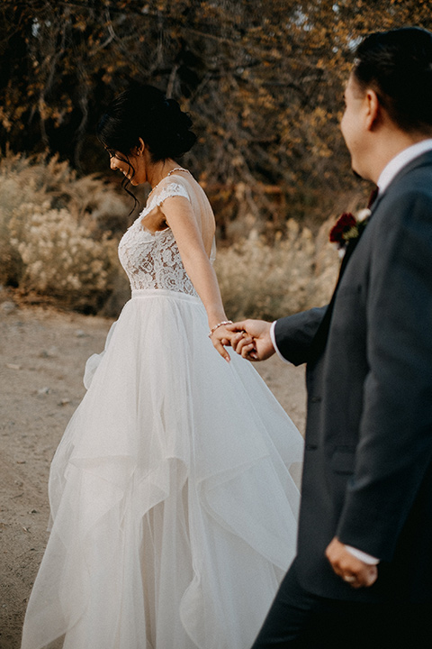 the-guest-ranch-bride-and-groom-walking-holding-hands-groom-in-a-dark-grey-suit-with-light-grey-vest-and-burgundy-bow-bride-in-a-tulle-ball-gown-with-straps-and-a-beaded-bodice
